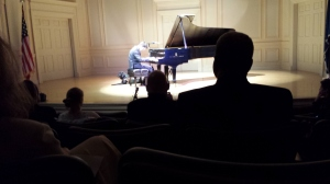 Justin Kauflin playing piano on stage. Candy sits on his left.