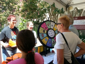 Four people stand around the Wheel of Justice, a spinning wheel featuring ADA-related topics.