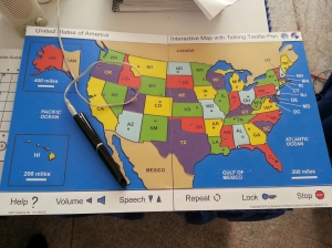 Interactive map of the United States from Touch Graphics and the American Printing House for the Blind uses a talking tactile pen. Each state has an interactive dot to play information. Additional commands at the bottom say help, volume, speech up or down, repeat, lock, and stop.