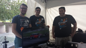 Three men representing AbleGamers with t-shirts saying everyone can game. A monitor shows a driving game with an accessible controller.