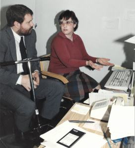 Mark Odum, sitting in a scooter next to a woman who is gesturing to a computer on a desk. The desk is covered in papers and a white push-button telephone.