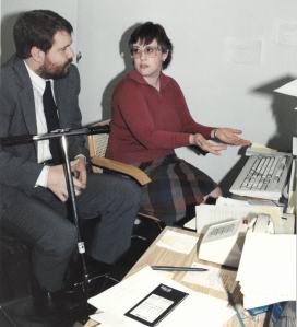 Mark Odum, sentado en un scooter junto a una mujer que está haciendo un gesto hacia una computadora en un escritorio. El escritorio está cubierto de papeles y yn teléfono con botones blancos.